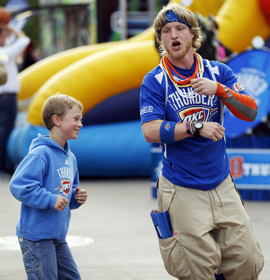 Photo - Gus Olson, right, a member of the Storm Chasers, dances with Braden Hinton, 8, of Weatherford, Okla., in Thunder Alley before Game 5 in the first round of the NBA playoffs between the Oklahoma City Thunder and the Memphis Grizzlies at Chesapeake Energy Arena in Oklahoma City, Tuesday, April 29, 2014. Photo by Nate Billings, The Oklahoman