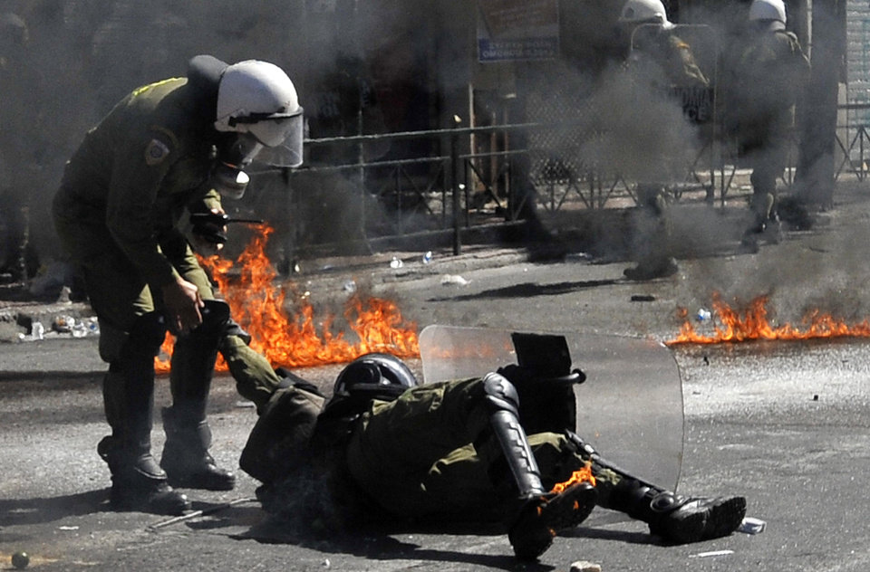 Photo -   A riot policeman assists a colleague after he was hit by a petrol bomb thrown by protester during clashes in Athens Wednesday Sept. 26, 2012. Greek workers walked off the job Wednesday for the first general strike since the country's coalition government was formed in June, as the prime minister and finance minister hammered out a package of euros 11.5 billion ($14.87 billion) in spending cuts. Athens has struggled to come up with more punishing austerity measures that would be acceptable to its rescue creditors, with disagreements arising between the three parties that make up the coalition government. Greece's creditors have demanded more fiscal reforms if they are to continue handing out rescue loans preventing the country from a messy default that could roil the euro. (AP Photo/Nikolas Giakoumidis)