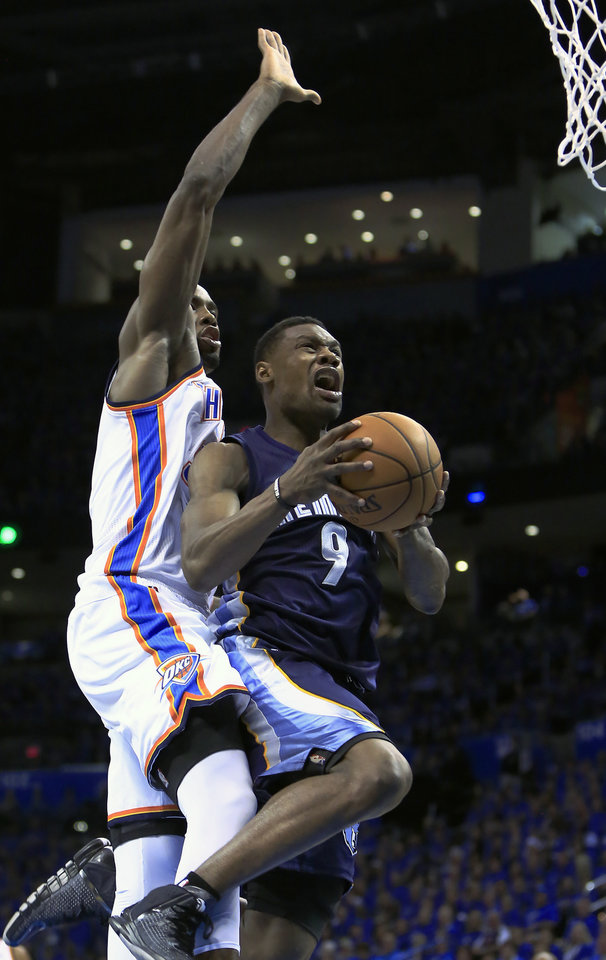 Photo - Memphis Grizzlies guard Tony Allen (9) goes to the basket in front of Oklahoma City Thunder forward Serge Ibaka (9) during the second quarter of Game 1 of the opening-round NBA basketball playoff series in Oklahoma City on Saturday, April 19, 2014. (AP Photo/Alonzo Adams)