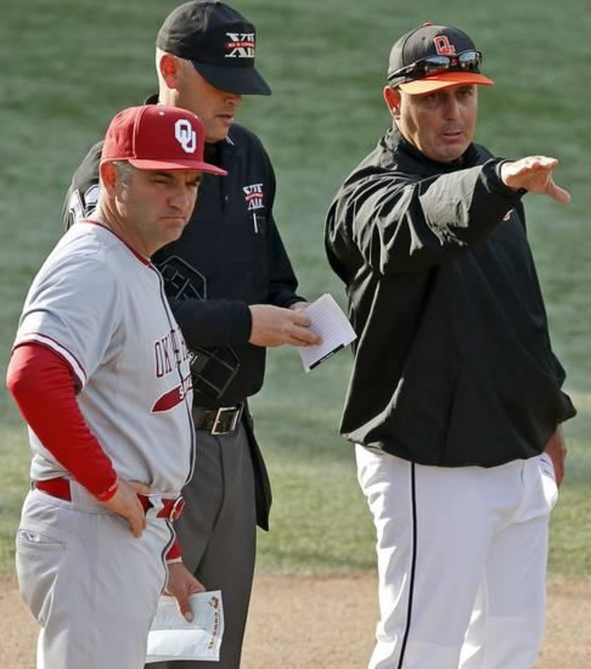 Photo - OU coach Pete Hughes and OSU coach Josh Holiday meet at home plate before a Bedlam baseball game between Oklahoma State University and the University of Oklahoma in Stillwater, Okla.,Tuesday, April 15, 2014. Photo by Bryan Terry, The Oklahoman