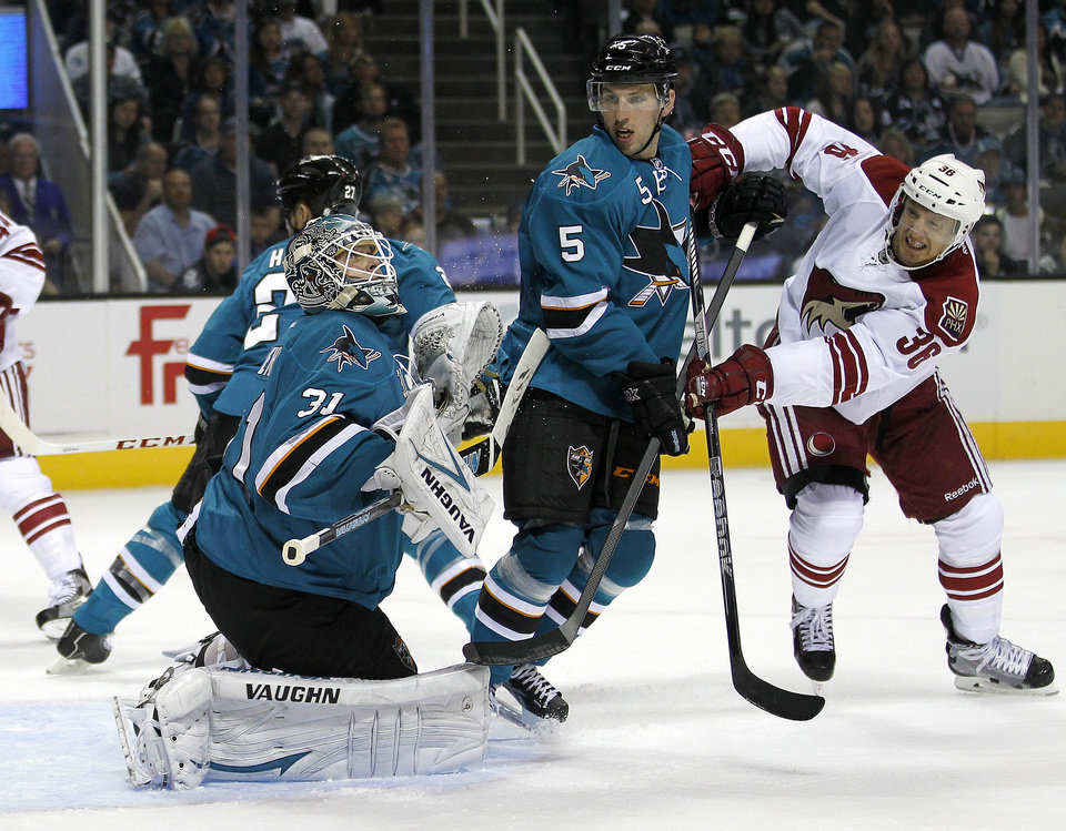 San Jose Sharks goalie Antti Niemi (31) block a goal attempt by Phoenix Coyotes left wing Rob Klinkhammer (36) as San Jose Sharks defenseman Jason Demers (5) defends  during the second period an NHL hockey game in San Jose, Calif., Saturday, Oct. 5, 2013. (AP Photo/Tony Avelar)