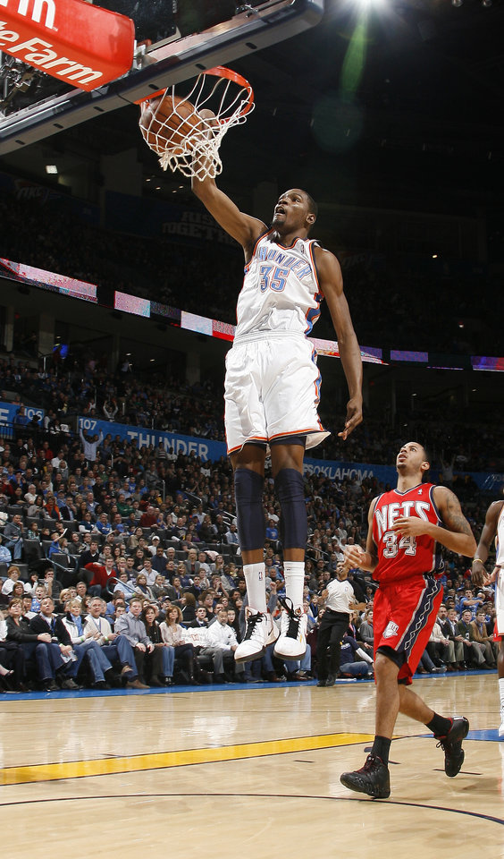 Photo - Oklahoma CIty's Kevin Durant dunks the ball in front of New Jersey's Devin Harris during the NBA basketball game between the Oklahoma City Thunder and the New Jersey Nets at the Oklahoma City Arena, Wednesday, Dec. 29, 2010.  Photo by Bryan Terry, The Oklahoman