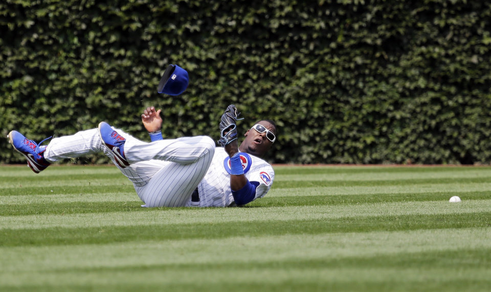 Photo - Chicago Cubs center fielder Junior Lake can' t make the play on a single hit by Colorado Rockies' Wilin Rosario during the fifth inning of a baseball game in Chicago, Thursday, July 31, 2014. (AP Photo/Nam Y. Huh)