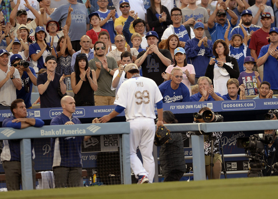 Photo - Fans cheer as Los Angeles Dodgers starting pitcher Hyun-Jin Ryu leaves the field after being relieved in the eighth inning of a baseball game against the Cincinnati Reds, Monday, May 26, 2014, in Los Angeles. The Dodgers won 4-3. (AP Photo/Gus Ruelas)