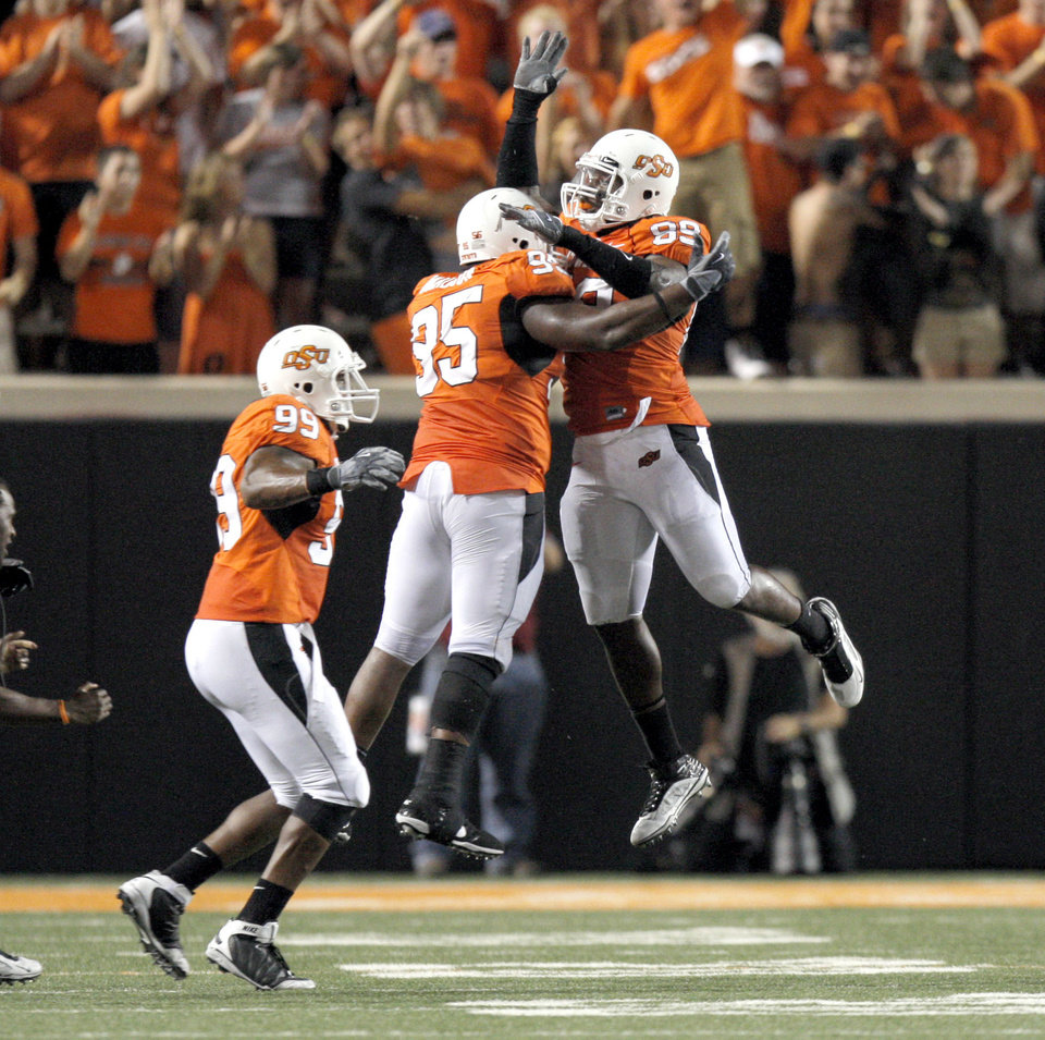 Photo - OSU's Richetti Jones (99), Montra Nelson (85) and Kevin Johnson (88) celebrate a fumble recovery during the college football game between the Oklahoma State University Cowboys (OSU) and the Troy University Trojans at Boone Pickens Stadium in Stillwater, Okla., Saturday, Sept. 11, 2010. Photo by Sarah Phipps, The Oklahoman