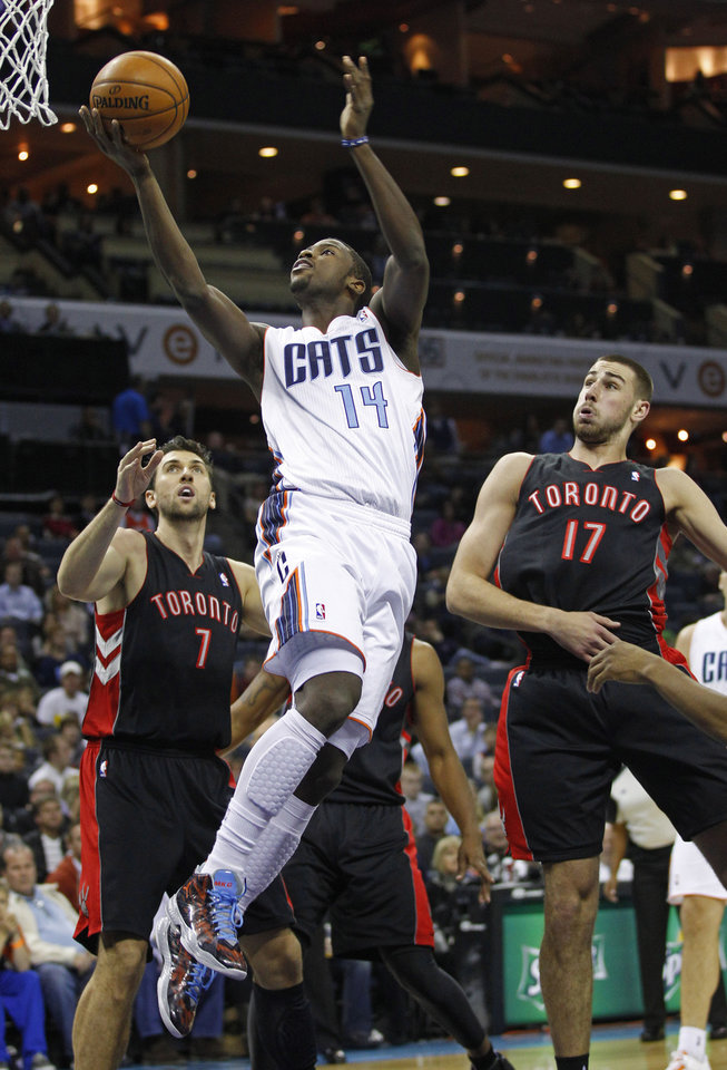 Photo -   Charlotte Bobcats' Michael Kidd-Gilchrist (14) drives between Toronto Raptors' Jonas Valanciunas (17) and Andrea Bargnani (7) during the first half of an NBA basketball game in Charlotte, N.C., Wednesday, Nov. 21, 2012. (AP Photo/Chuck Burton)