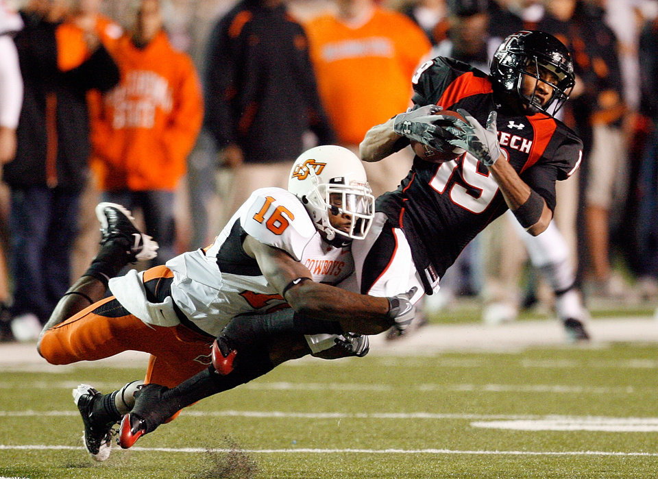Photo - Lyle Leong catches a pass and is tackled by Perrish Cox during the first half of the college football game between the Oklahoma State University Cowboys (OSU) and the Texas Tech Red Raiders at Jones AT&T Stadium on Saturday, Nov. 8, 2008, in Lubbock, Tex.By Steve Sisney/The Oklahoman