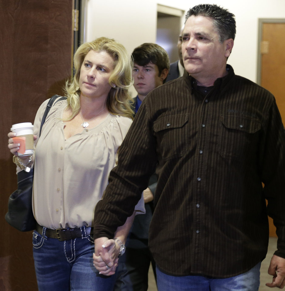 Photo - Steve Hernandez, right, the father of Rebecca Wingos who was killed in the Aurora theater, holds hands with an unidentified woman as they arrive for a court proceeding for Aurora theater shooting suspect James Holmes at the courthouse in Centennial, Colo., on Friday, Jan. 11,  2013. Hernandez yelled out