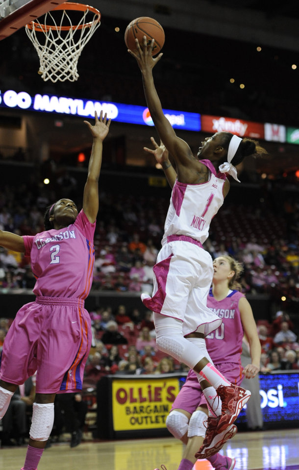 Photo - Maryland's Laurin Mincy, right, shoots as Clemson's Chelsea Lindsay tries to block in the second half of an NCAA college basketball game on Sunday, Feb. 9, 2014, in College Park, Md. Maryland won 95-43. (AP Photo/Gail Burton)