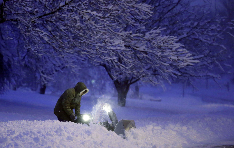 Photo - A local resident clears snow from his driveway after an overnight snowfall left many schools and businesses closed for the day, Thursday, Dec. 20, 2012, in Urbandale, Iowa. (AP Photo/Charlie Neibergall)