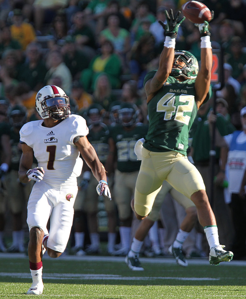 Photo - Baylor wide receiver Levi Norwood (42) catches a touchdown pass against Louisiana-Monroe safety Isaiah Newsome (1) in the second half of an NCAA college football game, Saturday, Sept. 21, 2013, in Waco, Texas. (AP Photo/Waco Tribune Herald, Jerry Larson)