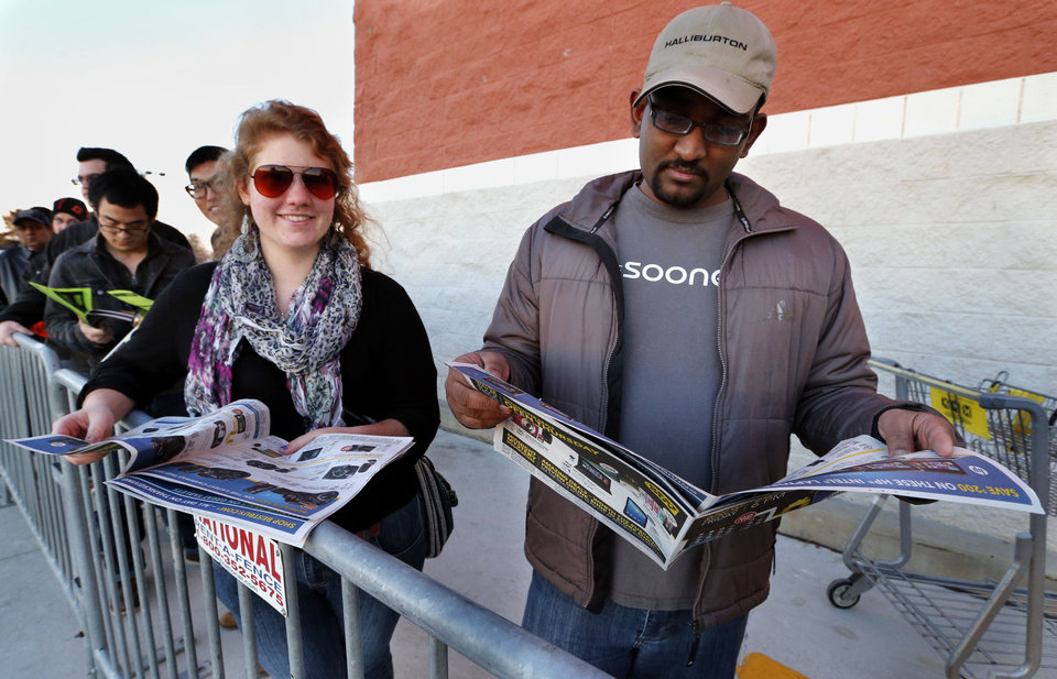Photo - Shoppers Liz Hodgson and Vividh Vijay get an early start on Black Friday as they wait in line at Best Buy on Thursday, Nov. 28, 2013, in Norman, Okla.  Photo by Steve Sisney, The Oklahoman