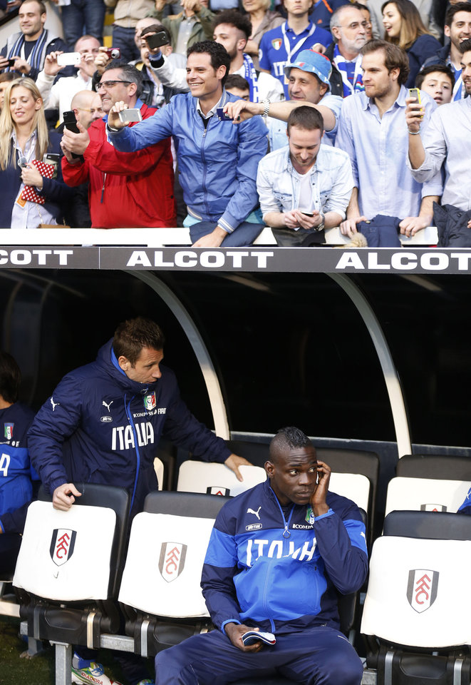 Photo - Italy's Mario Balotelli, lower right, looks on from the dugout as supporters, top, watch the players arrive at the dugout before the start of their international friendly soccer match against Republic of Ireland at Craven Cottage, London, Saturday, May 31, 2014. (AP Photo/Sang Tan)
