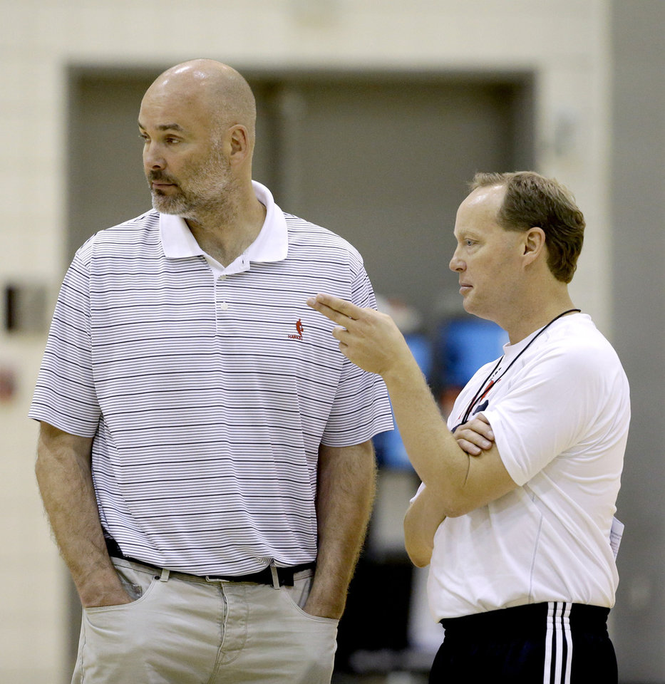 Photo - Atlanta Hawks head coach Mike Budenholzer, right, talks to general manager Danny Ferry during NBA basketball training camp, Tuesday, Oct. 1, 2013, in Athens, Ga. (AP Photo/David Goldman)