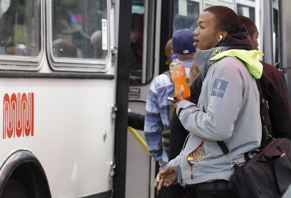 Photo -   A man holds a soft-drink bottle as he waits to board a Muni bus in San Francisco.    Jeff Chiu