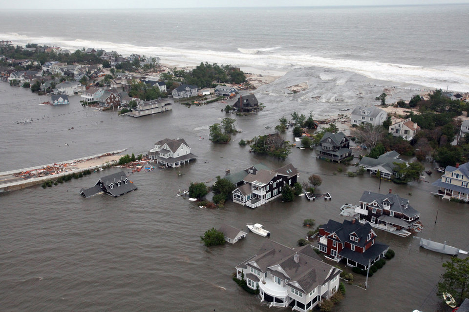 Photo - FILE - This Oct. 30, 2012 aerial file photo provided by the U.S. Air Force shows flooding on the New Jersey shoreline during a search and rescue mission by the New Jersey Army National Guard following Superstorm Sandy. Redrawn federal maps indicating flood-prone areas may force many property owners, especially in New York or New Jersey, to pay exorbitantly for flood insurance, raise their homes or move away altogether. In New Jersey, flood insurance premiums could cost as much as $31,000 a year. (AP Photo/U.S. Air Force, Master Sgt. Mark C. Olsen, File)