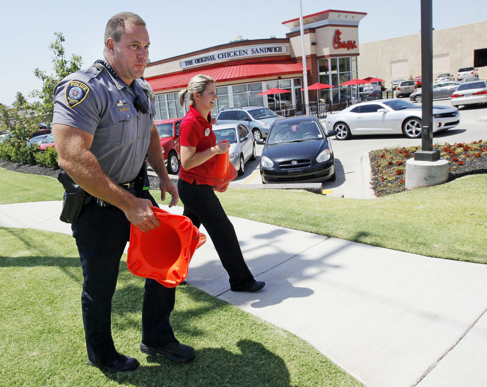 Photo - Oklahoma City Police Sgt. Von Tungeln and a Chick-fil-A employee who asked not to be identified take traffic cones at a Chick-fil-A at 6201 N May to block entry to the parking lot from May to prevent traffic from backing up into the intersection of NW 63rd and May at lunchtime during Chick-fil-A Appreciation Day in Oklahoma City, Wednesday, Aug. 1, 2012. Photo by Nate Billings, The Oklahoman