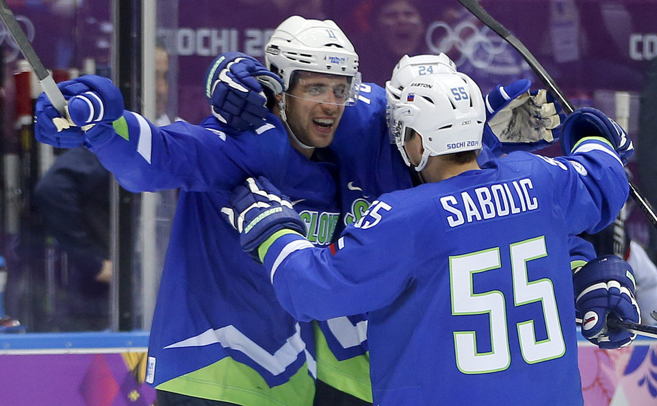 Photo - Slovenia forward Anze Kopitar, left, forward Robert Sabolic (55) and Slovenia forward Rok Ticar celebrate after a third period goal against Slovakia during a men's ice hockey game at the 2014 Winter Olympics, Saturday, Feb. 15, 2014, in Sochi, Russia. (AP Photo/Julio Cortez)