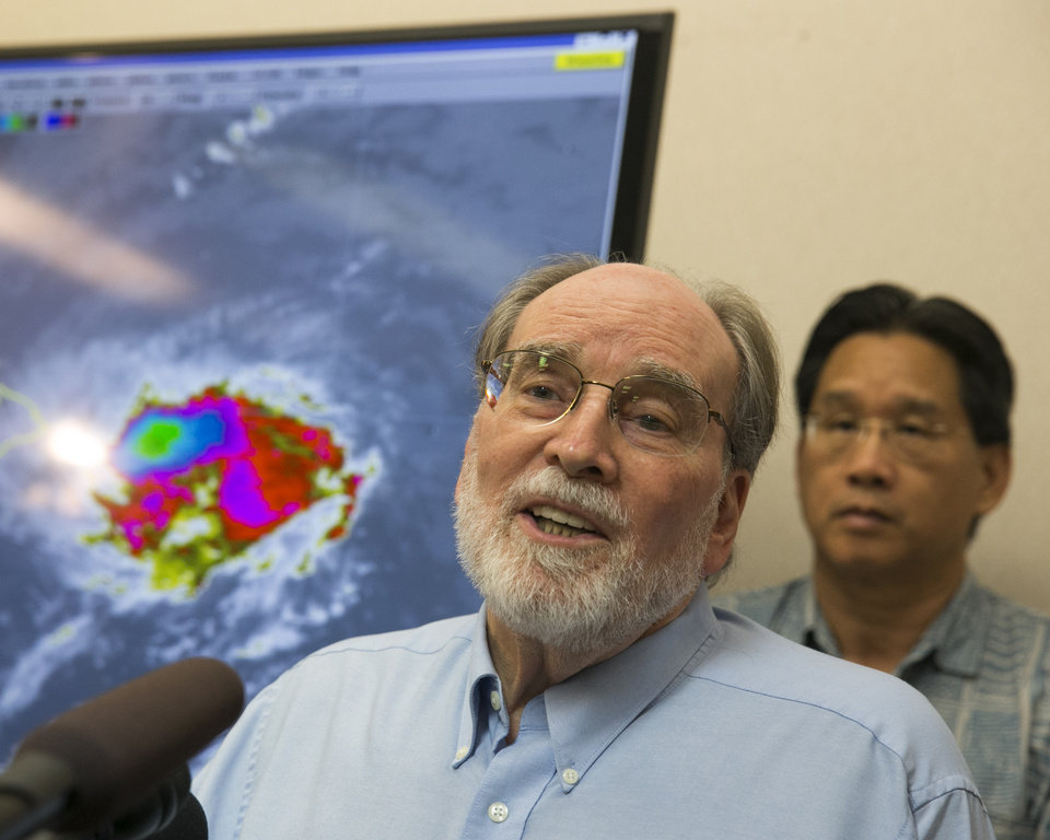 Photo - Hawaii Gov. Neil Abercrombie, center, speaks at the National Weather Service office on the campus of the University of Hawaii, Thursday, Aug. 7, 2014, in Honolulu.  Hawaii is bracing for both Hurricane Iselle and Julio which are on course to hit the Hawaiian Islands. (AP Photo/Marco Garcia)