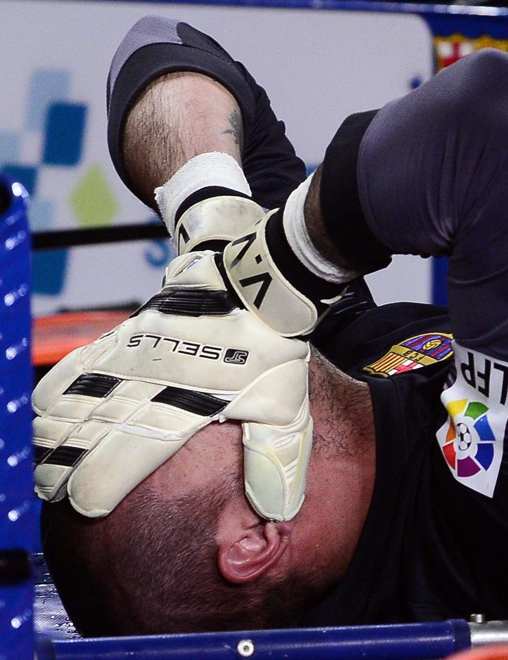 Photo - FC Barcelona's goalkeeper Victor Valdes reacts after being injured during a Spanish La Liga soccer match against Celta Vigo at the Camp Nou stadium in Barcelona, Spain, Wednesday, March 26, 2014. (AP Photo/Manu Fernandez)