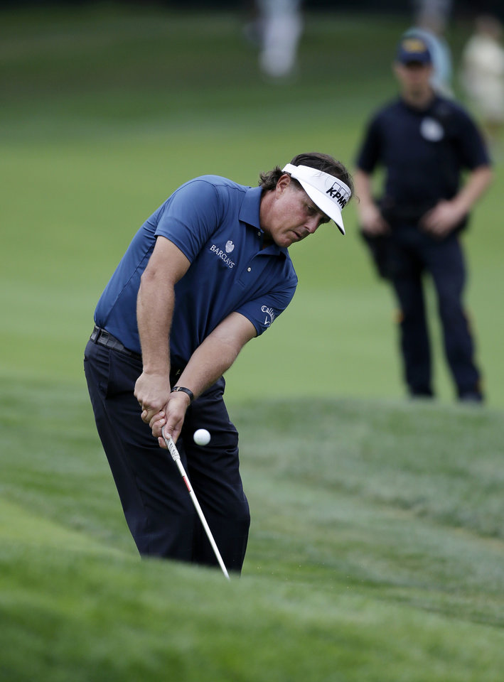 Photo - Phil Mickelson chips onto the 17th green during the first round of play at The Barclays golf tournament Thursday, Aug. 21, 2014, in Paramus, N.J.  (AP Photo/Mel Evans)