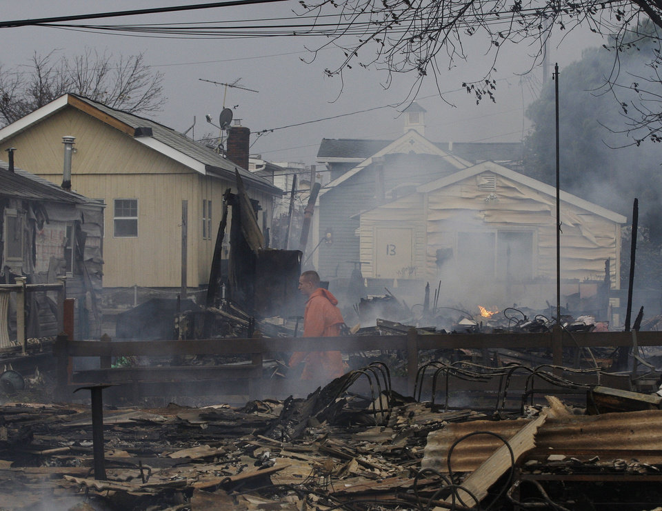 Photo -   Keith Klein walks through homes damaged by a fire at Breezy Point in the New York City borough of Queens. Tuesday, Oct. 30, 2012. The fire destroyed between 80 and 100 houses Monday night in an area flooded by the superstorm that began sweeping through earlier. (AP Photo/Frank Franklin II)