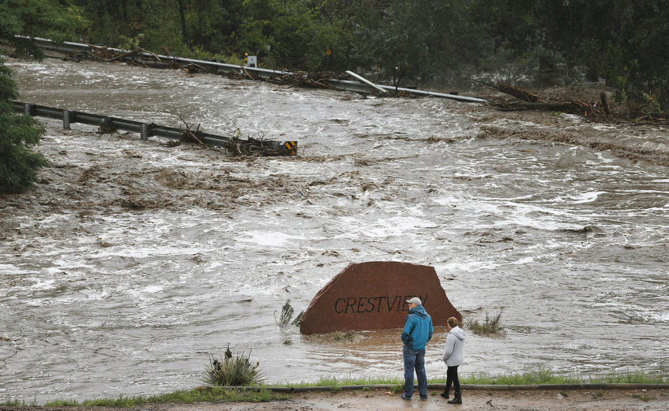 Photo - Local residents look over a road washed out by a torrent of water following overnight flash flooding near Left Hand Canyon, south of Lyons, Colo., Thursday, Sept 12, 2013. The widespread high waters are keeping search and rescue teams from reaching stranded residents in Lyons and nearby mountain communities as heavy rains hammered northern Colorado. (AP Photo/Brennan Linsley)