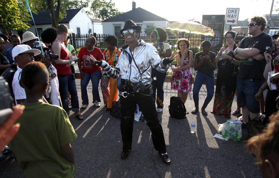 Photo -   Michael Jackson impersonator Dominique Wilson performs to recorded music outside Jackson's boyhood home during celebrations marking what would have been Jackson's 54th birthday Wednesday, Aug. 29, 2012, in Gary, Ind. (AP Photo/Charles Rex Arbogast)