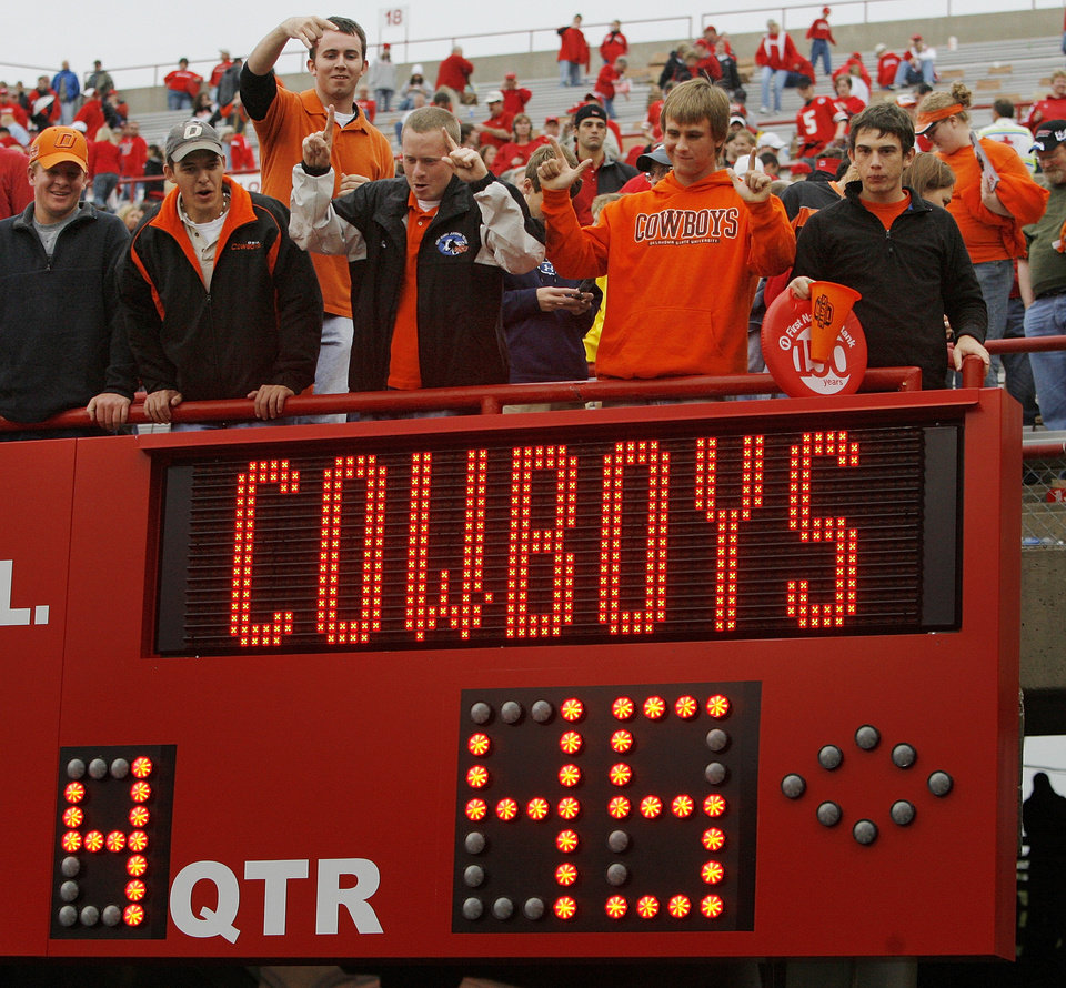 Photo - OSU fans celebrate over one of the scoreboards after the college football game between Oklahoma State University (OSU) and the University of Nebraska (NU) at Memorial Stadium in Lincoln, Neb., Saturday, October 13, 2007. OSU won, 45-14. By Nate Billings, The Oklahoman