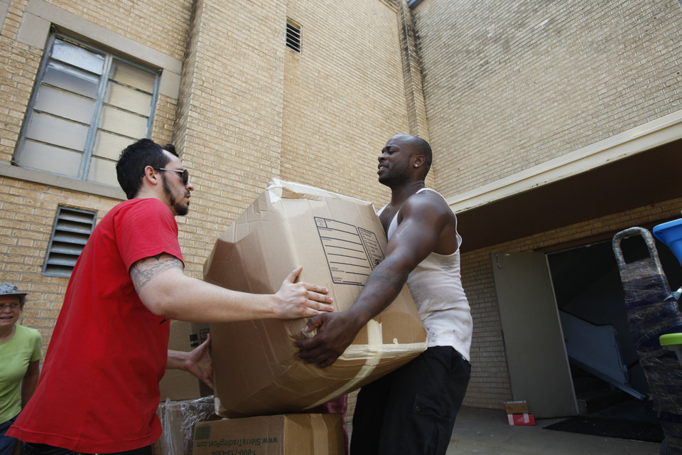 Photo - Stevan Correa of Brasilia, Brazil, hands off a box of donations for tornado victims to Sterling Hampton of Oklahoma City at Christ United Methodist Church, 1006 NE 17 in Oklahoma City.  Aliki Dyer - The Oklahoman