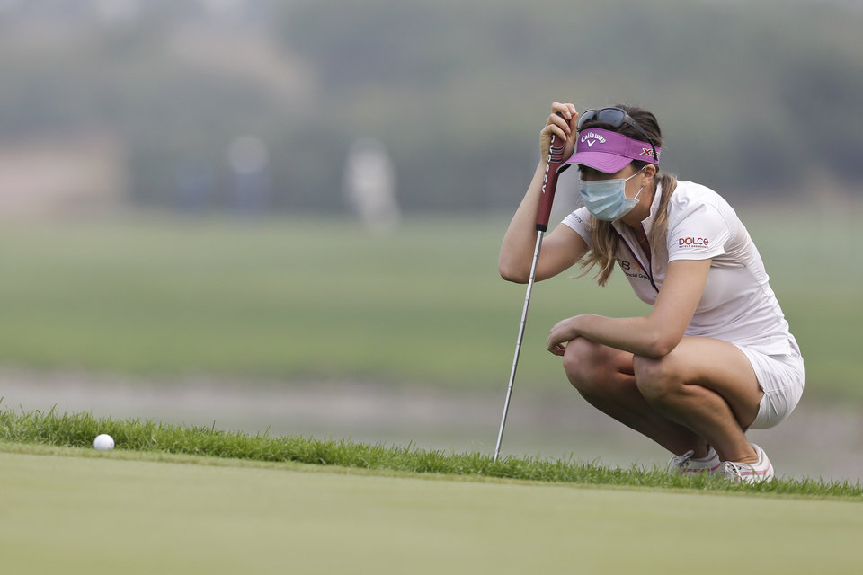 Germay's Sandra Gal, wearing a mask, lines up a putt on the third green on a hazy day during the final round of the Reignwood LPGA Classic golf tournament at Pine Valley Golf Club on the outskirts of Beijing, China, Sunday, Oct. 6, 2013. (AP Photo/Alexander F. Yuan)
