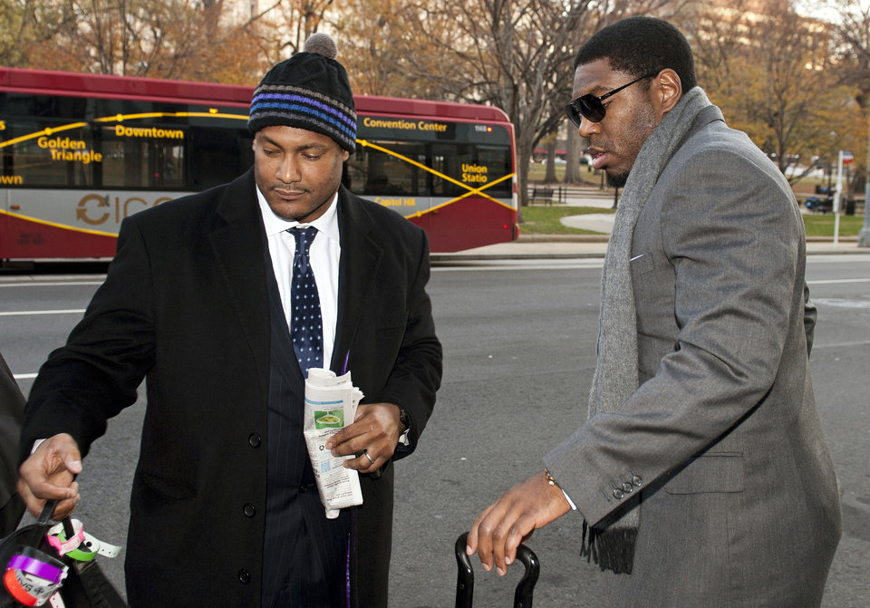 FILE - In this Nov. 30, 2012, file photo, New Orleans Saints football defensive end Will Smith, left, and linebacker Jonathan Vilma arrive at an attorney's office in Washington, for a hearing on their appeals of bounties suspensions. Former Commissioner Paul Tagliabue, who was appointed to handle a second round of player appeals to the league, has informed all parties he planned to rule by Tuesday, Dec. 11, and his decision could affect whether two current Saints — Jonathan Vilma and Will Smith — get to play out the season. (AP Photo/Cliff Owen, File)