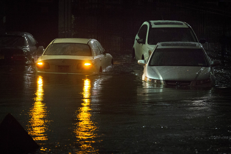 Vehicles are submerged during a storm surge near the Brooklyn Battery Tunnel, Monday, Oct. 29, 2012, in New York. Superstorm Sandy zeroed in on New York's waterfront with fierce rain and winds that shuttered most of the nation's largest city Monday, darkened the financial district and left a huge crane hanging off a luxury high-rise. (AP Photo/John Minchillo) ORG XMIT: NYJM123