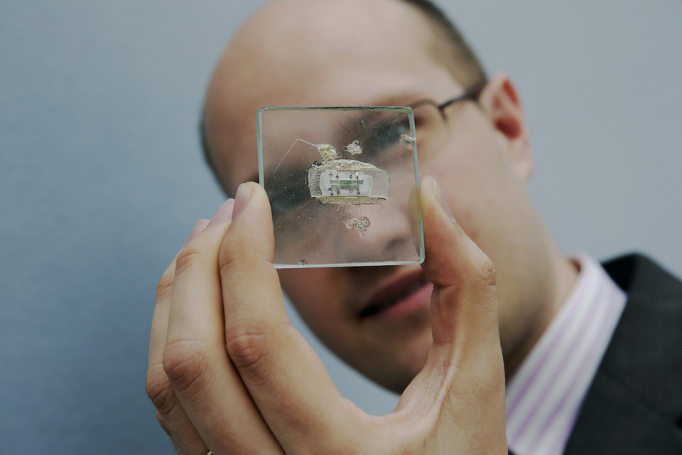 Photo - FILE - In this May 23, 2014 file photo, Christie's Head of Travel, Science and Natural History Sale James Hyslop poses for photographs with a 1958 prototype integrated circuit mounted on glass designed by Nobel Prize Physics winner Jack Kilby at Texas Instruments, at premises of the auction house in London, Friday, May 23, 2014.  The prototype microchip, a historical contribution to the modern computing era, is estimated to fetch between $1,000,000 and $2,000,0000 at a June 19 sale in New York.  (AP Photo/Matt Dunham, File)