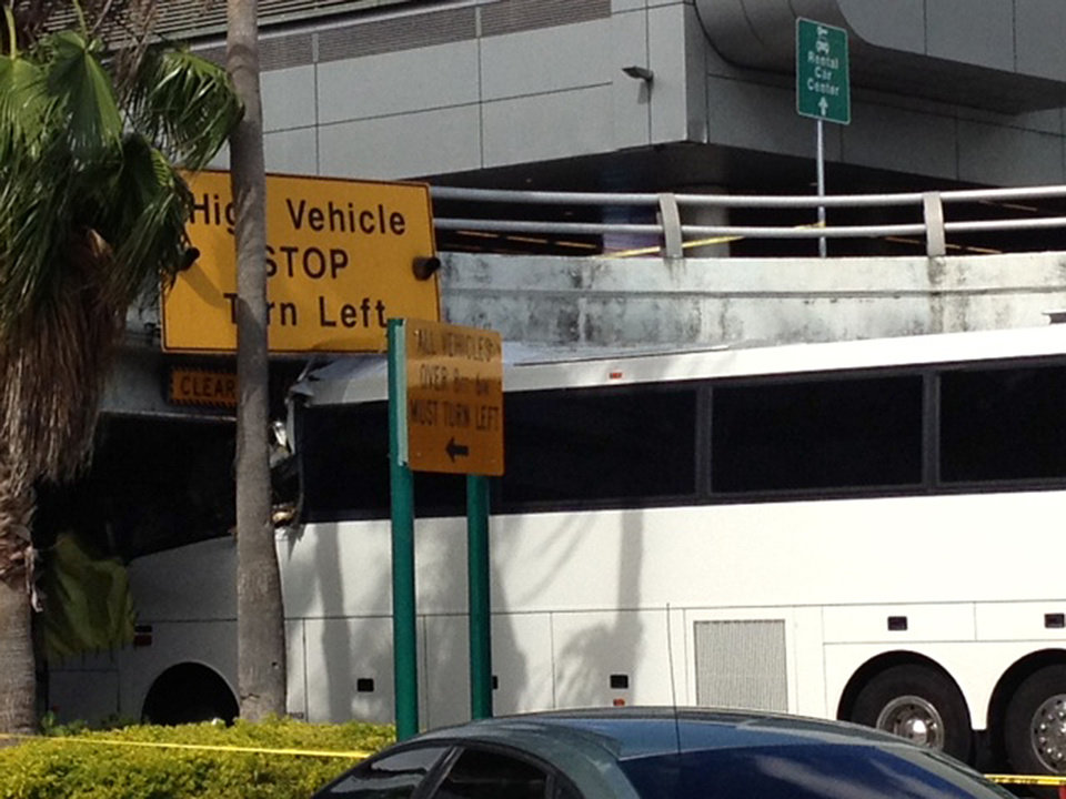 Photo - A bus is lodged into an overpass at the Miami International Airport on Saturday, Dec. 1, 2012. The vehicle was carrying over 30 people when it crashed into the structure. Authorities say buses typically are routed through the departures area, which has a higher clearance. (AP Photo/Suzette Laboy)