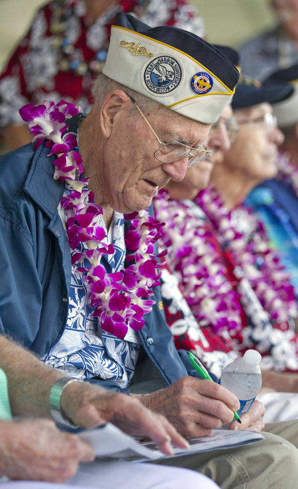 Photo - Pearl Harbor survivor Tom Berg, of Port Townsen, Wash., a sailor on the USS Tennessee, signs his autograph for an admirer Friday, Dec. 7, 2012, at Pearl Harbor, Hawaii. Many of the Pearl Harbor Veterans gathered at the World War II Valor In The Pacific National Monument remembering the 71th anniversary of the Dec. 7, 1941 Japanese surprise attack on Pearl Harbor in Honolulu. (AP Photo/Eugene Tanner)