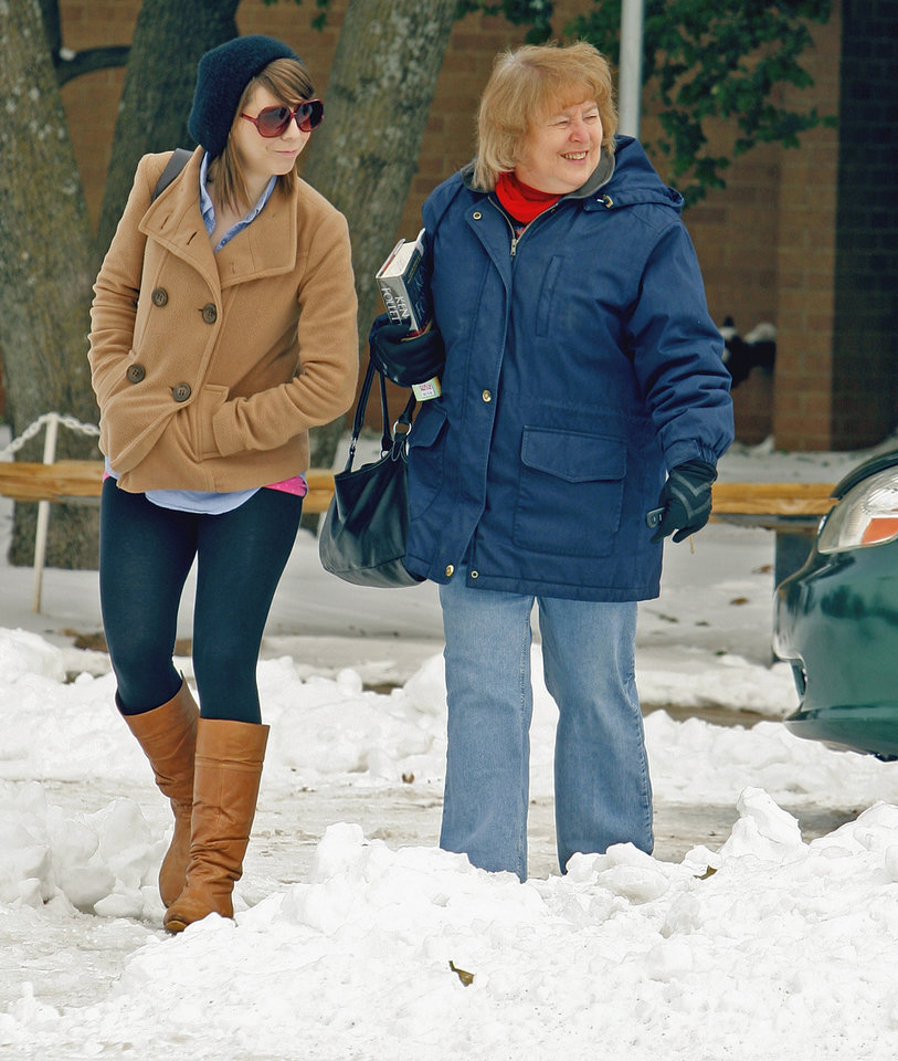 Photo - Allison Swenson and her mother Sue Swenson of Norman leave the Norman Public Library with books as patrons venture out after days of being cooped up by ice and snow on Thursday, February 3, 2011, in Norman, Okla.  Photo by Steve Sisney
