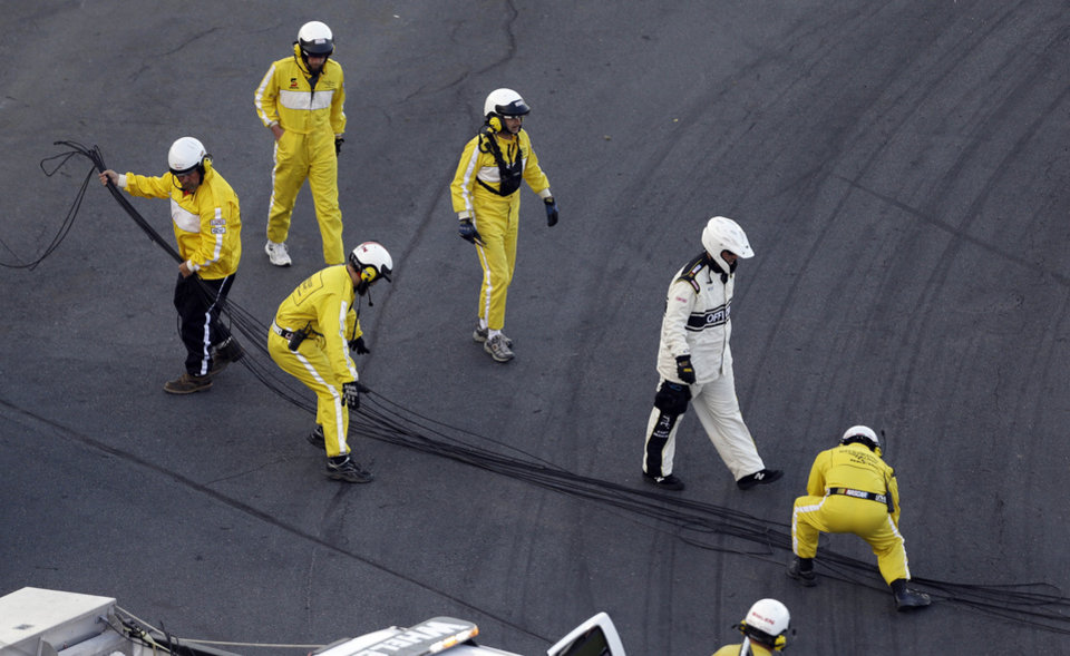 A crew gathers cable from a broken television camera rig during the NASCAR Sprint Cup Series Coca-Cola 600 auto race at the Charlotte Motor Speedway in Concord, N.C., Sunday, May 26, 2013. The race was red flagged temporarily and several cars were damaged after running over the cable. (AP Photo/Gerry Broome)