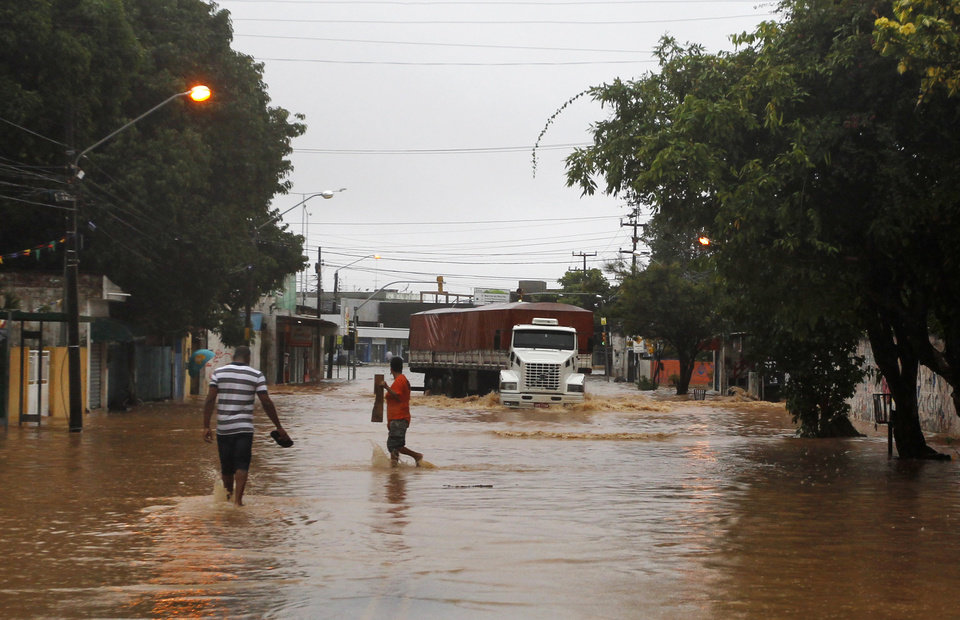 Photo - A truck makes it's way down a flooded street after heavy rain storms in Recife, Brazil, Thursday, June 26, 2014. The World Cup soccer match between the USA and Germany will be played at the Arena Pernambuco in Recife today.  (AP Photo/Petr David Josek)