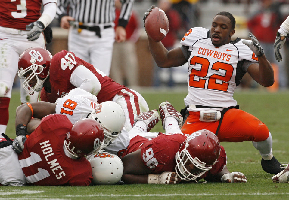 Photo - Oklahoma State's Dantrell Savage (22) gets out of the pile without his helmet during the first half of the college football game between the University of Oklahoma Sooners (OU) and the Oklahoma State University Cowboys (OSU) at the Gaylord Family-Memorial Stadium on Saturday, Nov. 24, 2007, in Norman, Okla. 