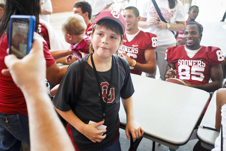 Photo - Jake Bowker, 10, of Midwest City has his picture taken in front of Ryan Broyles at the University of Oklahoma's Meet the Sooners Day at Gaylord Family