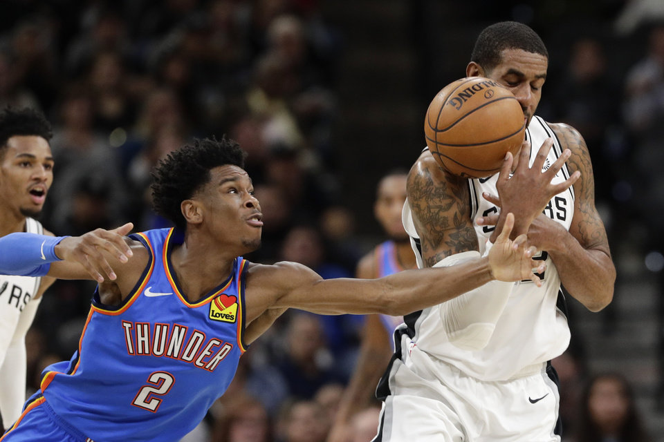 Photo - Oklahoma City Thunder guard Shai Gilgeous-Alexander (2) knocks the ball away from San Antonio Spurs center LaMarcus Aldridge (12) during the first half of an NBA basketball game, in San Antonio, Thursday, Jan. 2, 2020. (AP Photo/Eric Gay)