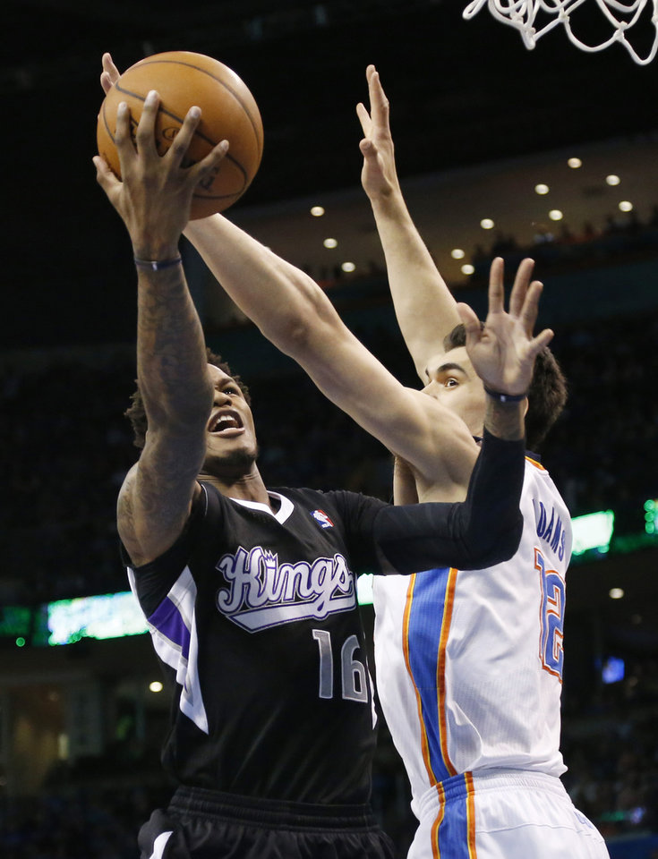 Photo - Sacramento Kings guard Ben McLemore (16) shoots in front of Oklahoma City Thunder center Steven Adams (12) during the first quarter of an NBA basketball game in Oklahoma City, Friday, March 28, 2014. Oklahoma City won 94-81. (AP Photo/Sue Ogrocki)