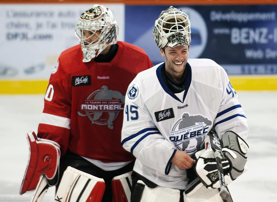 Los Angeles Kings goaltender Jonathan Bernier, right, laughs with Chicago Blackhawks goalie Cory Crawford following a charity hockey game in Chateauguay, Quebec, Thursday, Sept. 27, 2012. The NHL canceled the rest of the preseason Thursday, just a day before negotiations were set to resume in an effort to end the lockout. (AP Photo/The Canadian Press, Graham Hughes)
