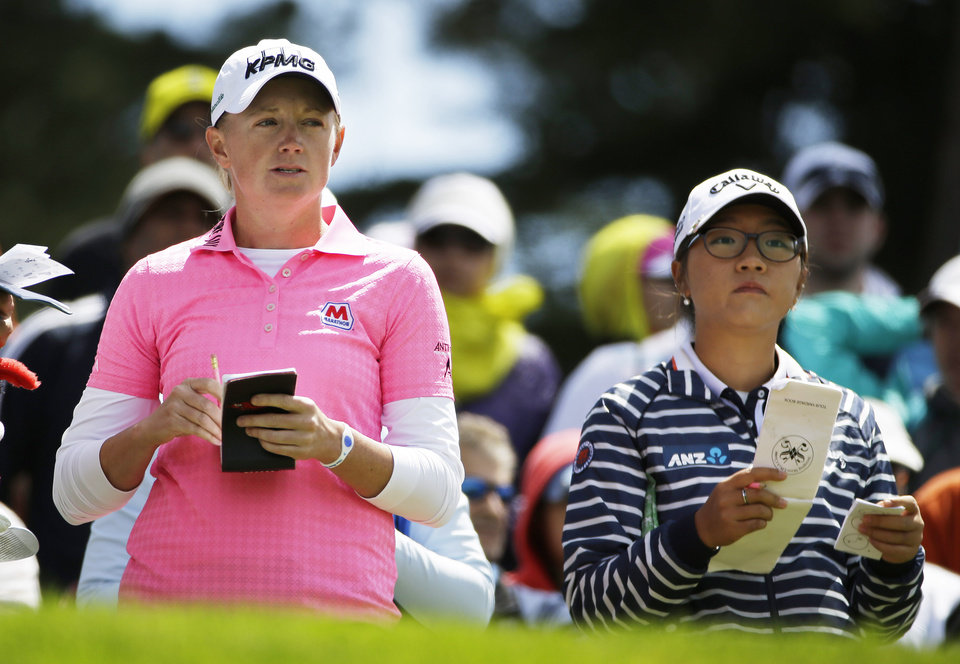 Photo - Stacy Lewis, left, and Lydia Ko, right, of New Zealand prepare to hit from the third tee of the Lake Merced Golf Club during the third round of the Swinging Skirts LPGA Classic golf tournament on Saturday, April 26, 2014, in Daly City, Calif. (AP Photo/Eric Risberg)