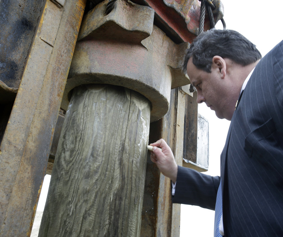 Photo - New Jersey Gov. Chris Christie signs the first piling of Belmar's new boardwalk construction Wednesday, Jan. 9, 2013, in Belmar, N.J. Belmar began construction on a 1.3-mile boardwalk to replace the walkway destroyed by Superstorm Sandy in October. The goal is to have it done by May. (AP Photo/Mel Evans)