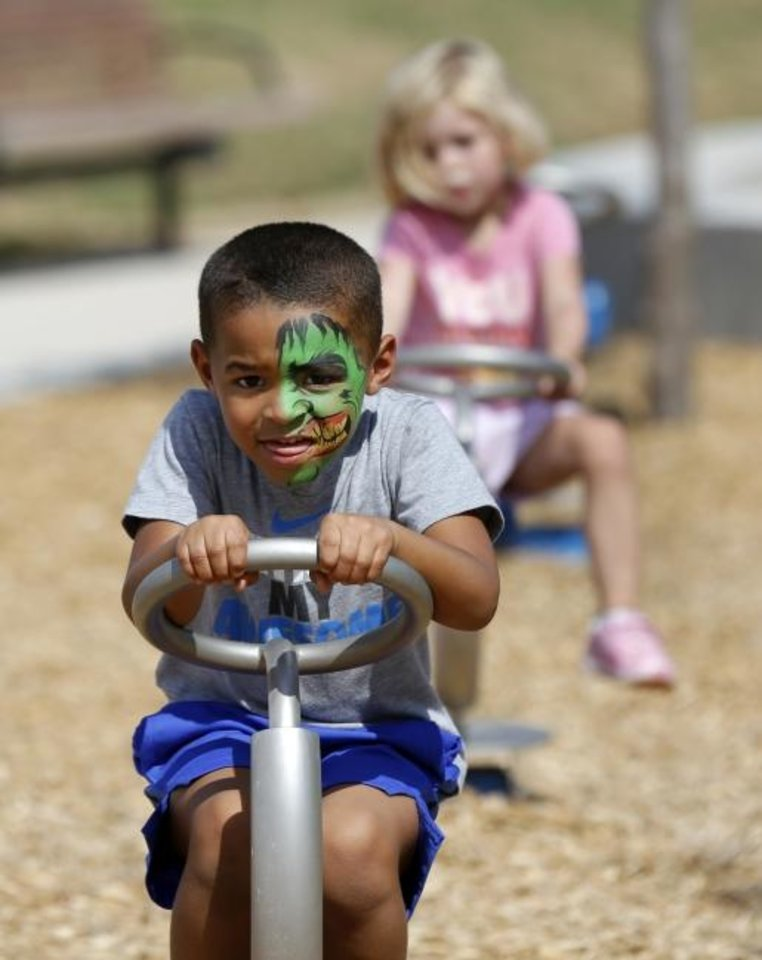 Photo -  Cason Young, 4, plays in the children's playground Saturday at Scissortail Park. [Nate Billings/The Oklahoman]