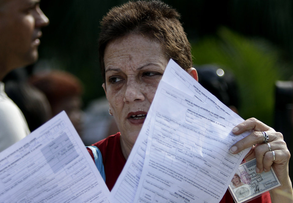 Photo - In this Jan. 7, 2013 photo, a woman holds papers after filling out a passport application outside an immigration office in Havana, Cuba. In the past nearly all exit visa applications were granted, and relatively quickly, but the costs were prohibitive to many in this country where wages average $20 a month. Between notarization and application fees, fees ran to $300 or more per trip, and some Cubans paid an additional $200 to $300 to people overseas for invitation letters. Now, with a new law taking effect Monday, Jan. 14, 203, islanders need only make a one-time $100 application for a passport, renewable for $20 every two years.  (AP Photo/Franklin Reyes)