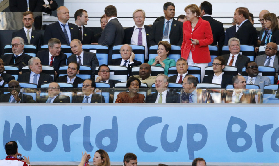 Photo - IOC president Thomas Bach, third row second left, Russian President Vladimir Putin, third left, FIFA President Sepp Blatter, fourth left, Brazil's President Dilma Rousseff, fourth right, German Chancellor Angela Merkel, standing, German President Joachim Gauck, second right, and South African President Jacob Zuma, right, wait for the beginning of the World Cup final soccer match between Germany and Argentina at the Maracana Stadium in Rio de Janeiro, Brazil, Sunday, July 13, 2014. (AP Photo/Frank Augstein)