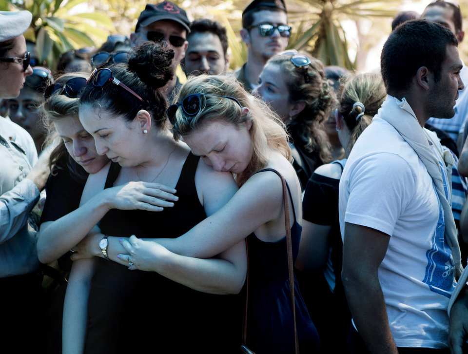 Photo - Family and friends of Maj. Tzafrir Bar-Or, 32, one of 13 soldiers killed in several separate incidents in Shijaiyah on Sunday, mourn during his funeral at the military cemetery in Holon, Monday, July 21, 2014. On Sunday, the first major ground battle in two weeks of Israel-Hamas fighting exacted a steep price, killing scores of Palestinians and more than a dozen Israeli soldiers and forcing thousands of terrified Palestinian civilians to flee their devastated Shijaiyah neighborhood, which Israel says is a major source for rocket fire against its civilians. (AP Photo/Dan Balilty)